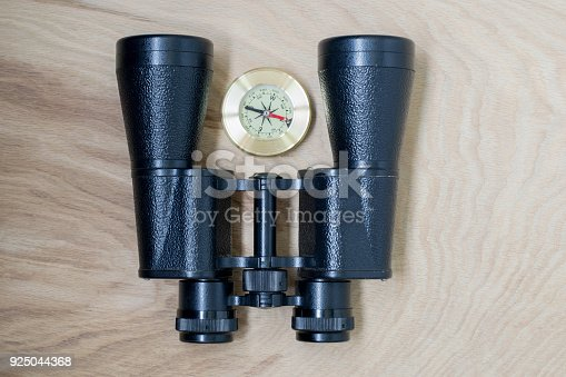 istock Binoculars and compass, traveler's things, on the wooden background 925044368