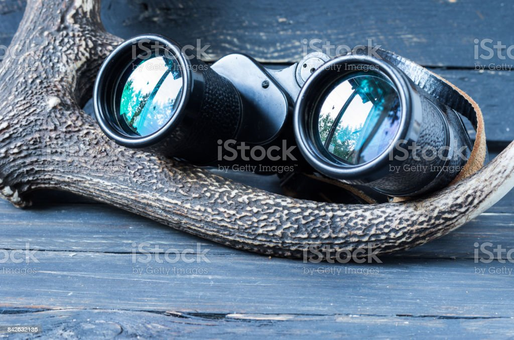 Binoculars and deer horn. Binoculars for tourists and hunters. stock photo