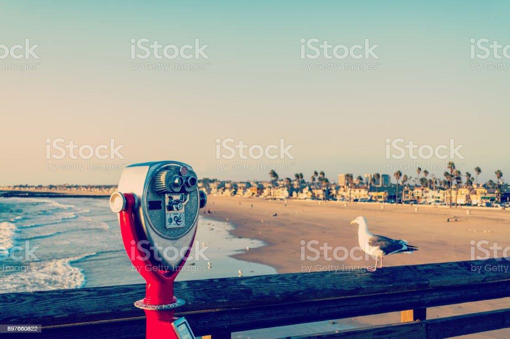 Binoculars and seagull in Newport Beach pier stock photo