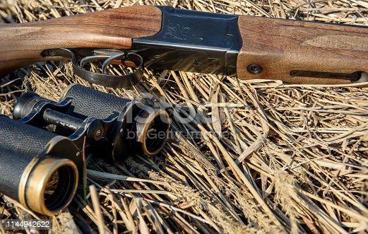 Binoculars and a hunting rifle lie on the dry grass. Hunter ammunition.