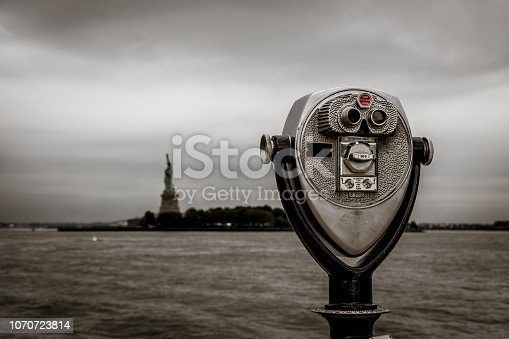 Binoculars in Ellis Island with view to the liberty statue new york
