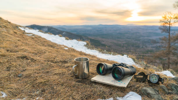 Binoculars map compass and mug on the background of nature mountains in the sunset. stock photo