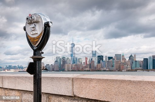 istock Binoculars on Ellis Island pointed towards Manhattan's skyline in a cloudy day 826038168