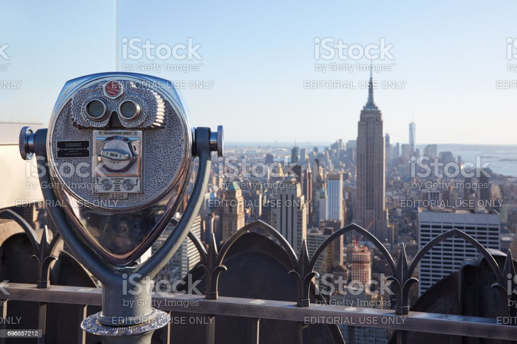 Binoculars on Rockefeller Center with Empire State Building and city view at the end of the day in New York stock photo