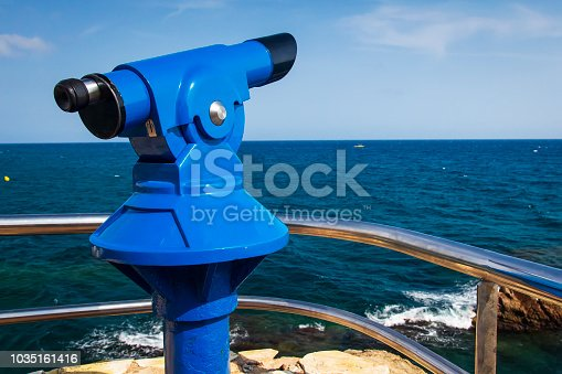 istock Binoculars on viewing platform on seafront in Lloret de Mar, Costa Brava, Catalonia, Spain. Mint binoculars on sea viewpoint. Telescope overlooking sea in Lloret de Mar. Catalonia, Spain, Europe 1035161416
