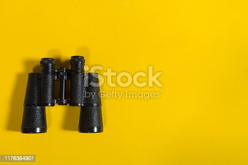 Black metalic binoculars on a yellow background