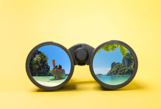 Binoculars on yellow background with tropic landscape reflection stock photo