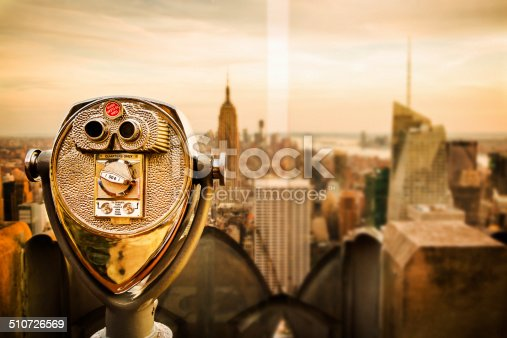 Binoculars and spectacular view over New York City, as seen from the Empire State Building observation deck, one of the main tourist attractions in New York City. Shot during sunset. Copy space on the left side.