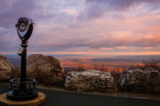 Binoculars point towards majestic sunset in purple tones overlooking the valley in winter