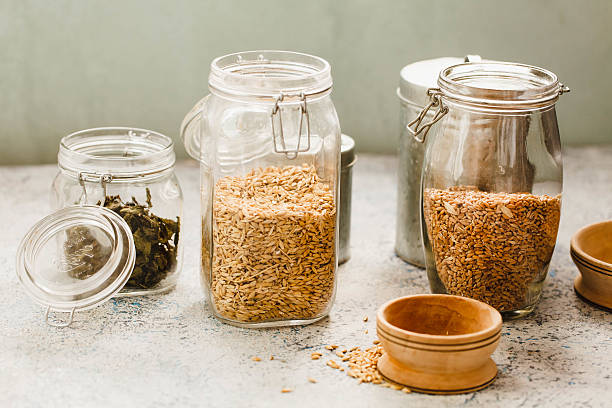 Bio Wheat And Oat Grains In Glass Jars Over Table stock photo