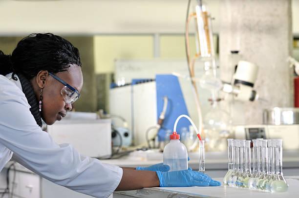 Biochemist decants fluid in flask side view stock photo