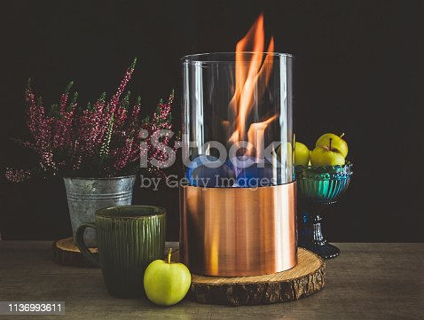 istock Bioethanol fueled portable fireplace burning at home, for live fire at home, no chimney and mantelpiece is needed. Liquid  bio ethanol burns in cup. Black background, green tea cup, apples in bowl. 1136993611