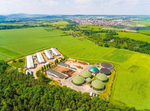 Biogas plant and farm in green fields. stock photo