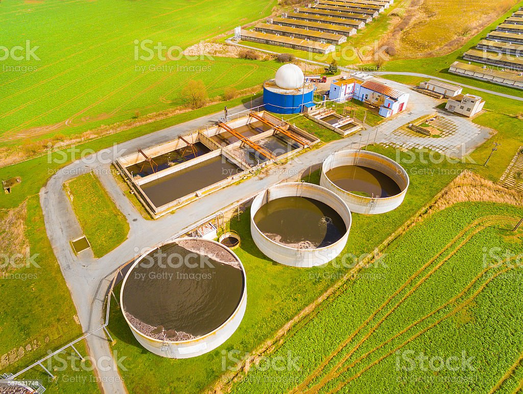Biogas plant and pig farm in green fields. stock photo