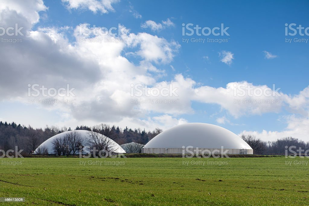 biogas plant behind a wide field against blue sky stock photo