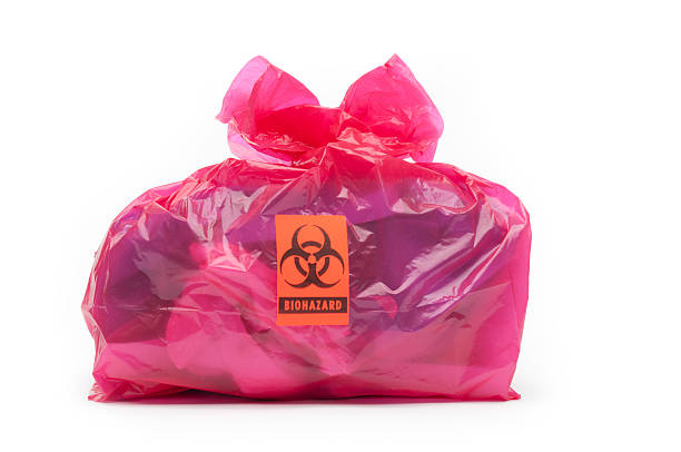 Bio-hazard bag/small A red bio-hazard bag containing medical waste with a bio-hazard label. Background is 255 white. toxic waste stock pictures, royalty-free photos & images