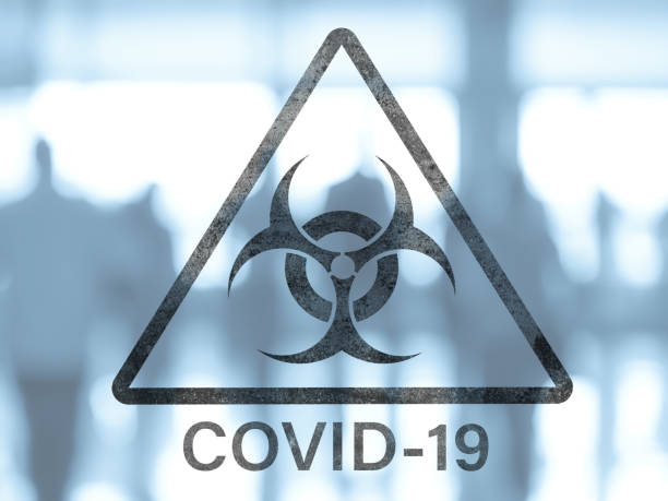 Biohazard dangerous sign COVID-19 triangle biohazard warning sign on a blurred background of the group of people in the public place covid icon stock pictures, royalty-free photos & images