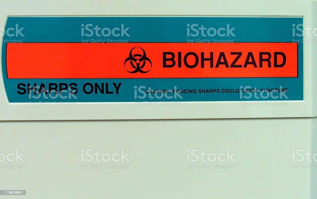 Biohazard label on sharps container in the medical office. royalty-free stock photo