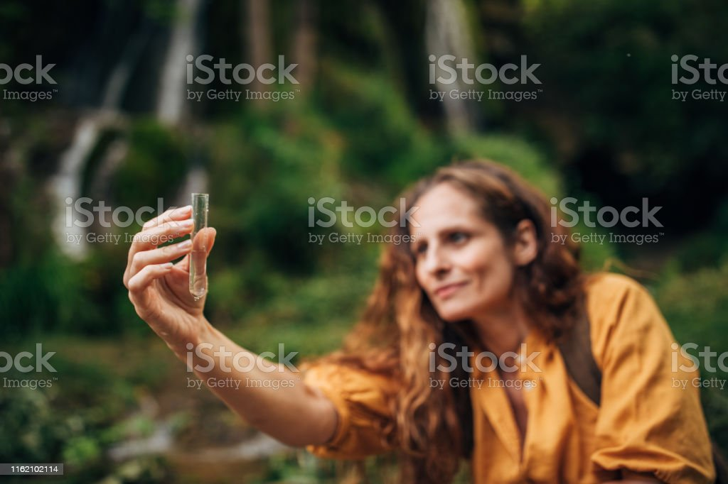 One woman, lady explorer and biologist taking a water sample in...