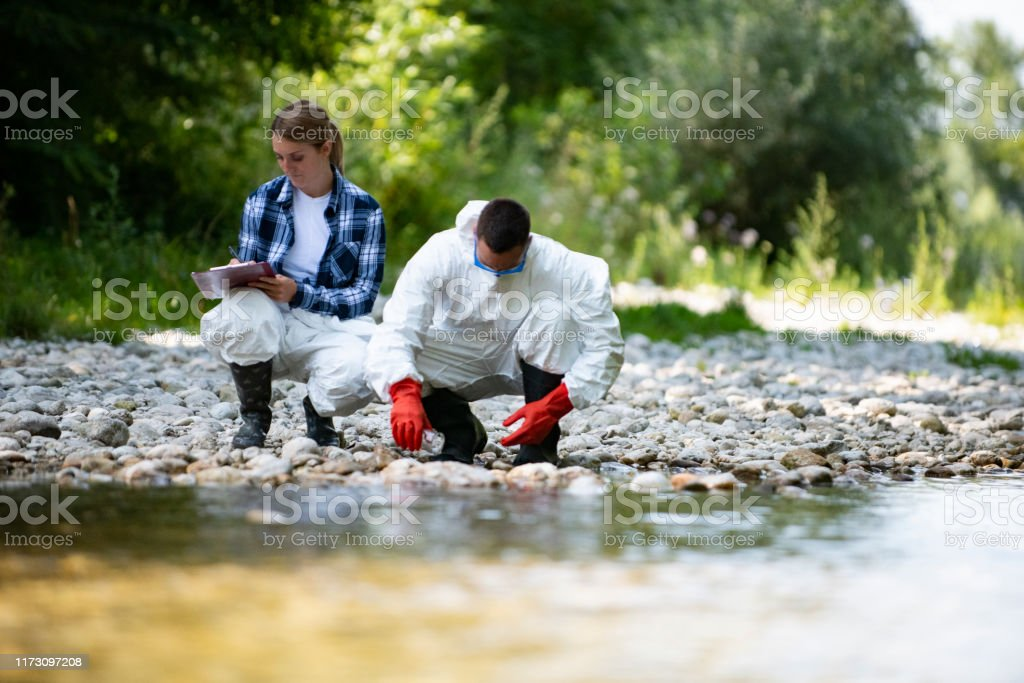Biologist takes water from a forest river to study the composition in the laboratory Biologist takes water from a forest river to study the composition in the laboratory Adult Stock Photo