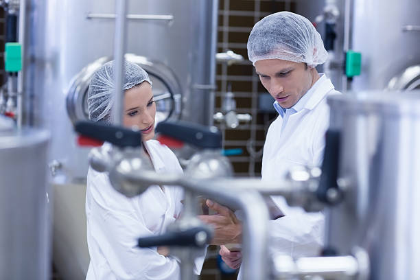 Biologist team talking and wearing hairnet Biologist team talking and wearing hairnet in the factory hair net stock pictures, royalty-free photos & images