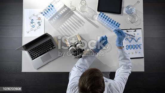 Biology student working with microscope, preparing sample to study, top view