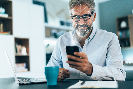 Facial recognition software scans the face of elegant senior man holding smart phone at home