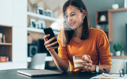 Facial recognition software scans the face of young woman holding smart phone at home