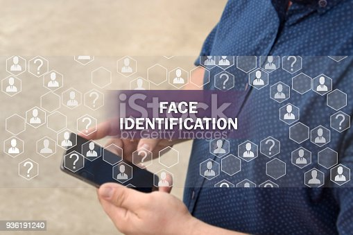 872707982 istock photo Biometric verification, face recognition technology.  Face identification Button on the touch screen with a blur background of the businessman with the phone.The concept of  face recognition technology 936191240