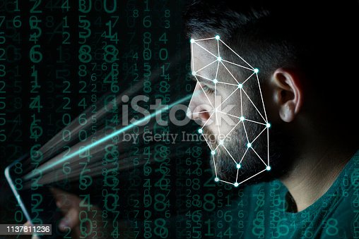 851960142 istock photo Biometrics identification and face detection verification concept. Unlocking smartphone with facial recognition technology in dark conditions. 1137811236