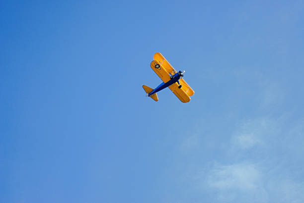 Biplane aircraft flying overhead in sky stock photo