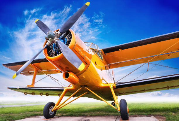 biplane biplane against a cloudy sky propeller stock pictures, royalty-free photos & images