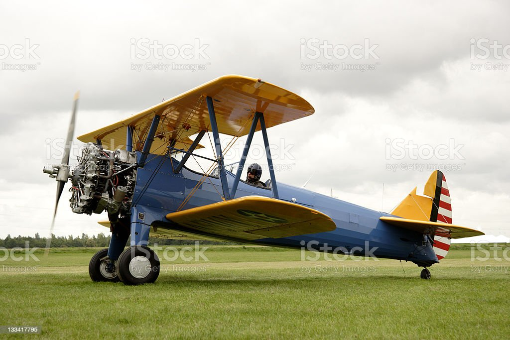Biplane starting up its engines in a field stock photo