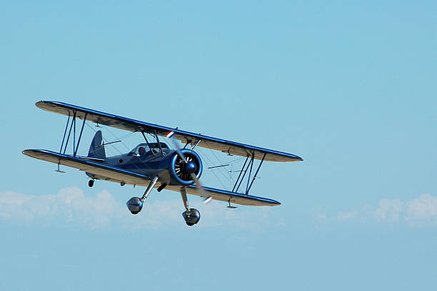 biplane Stearman Kadet flying in sky stock photo