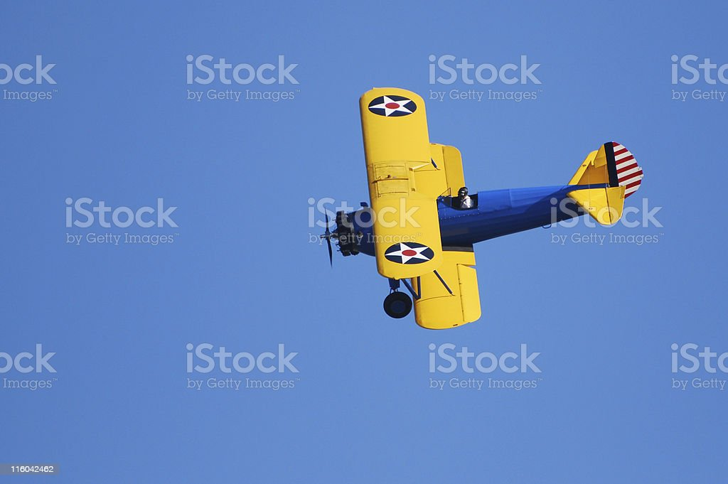WWII biplane Stearman PT17 Kaydet flying in clear blue sky stock photo