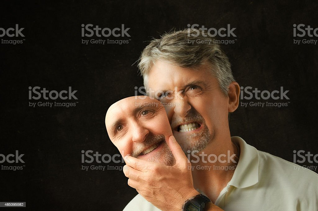 Bipolar disorder angry emotional man with fake smile mask stock photo