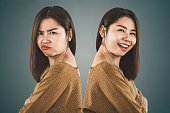 istock bipolar disorder personality. Asian woman face happy and depressed moods 1070834442