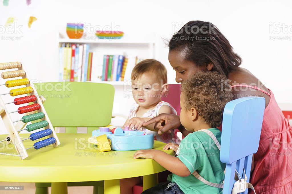 Biracial Baby Boy And His Peer Interacting With Their Carer royalty-free stock photo