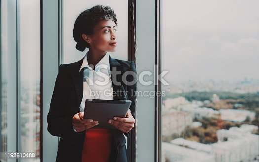 A dazzling young African-American woman entrepreneur with a digital tablet in her hands is standing near a huge panoramic window indoors of a business high-rise and pensively looking at the cityscape
