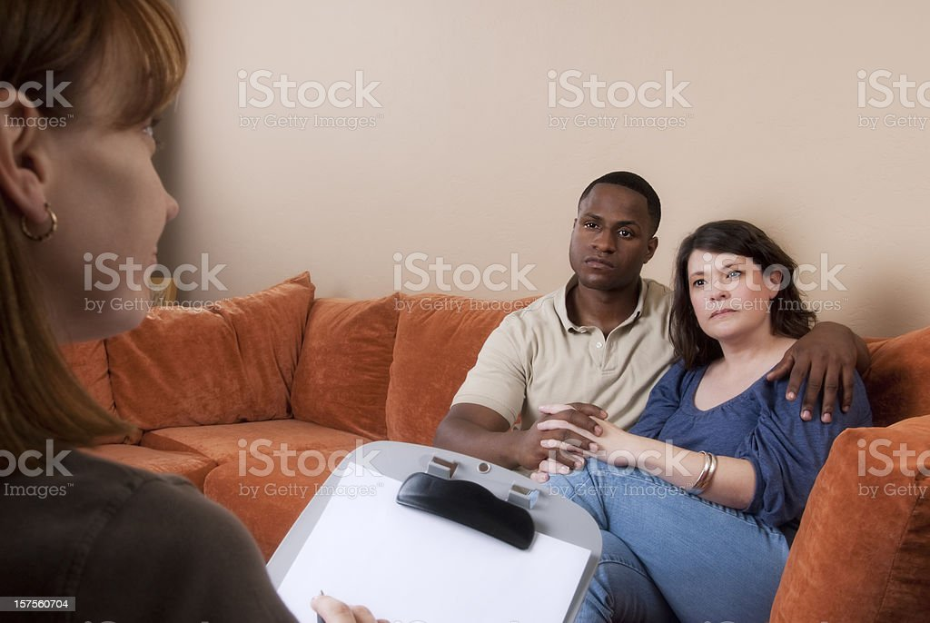 Bi-racial couple on the couch looking at consultant or therapist stock photo