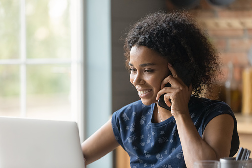 Modern way of communication. Smiling biracial female hold cell at ear talk look at pc screen. Busy young black lady advisor lawyer give phone consultation from home discuss electronic document details