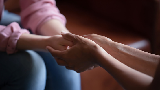 Professional assistance. Close up of biracial female psychologist therapist hands holding palms of millennial woman or teenage girl patient client talking consulting helping accept difficult situation