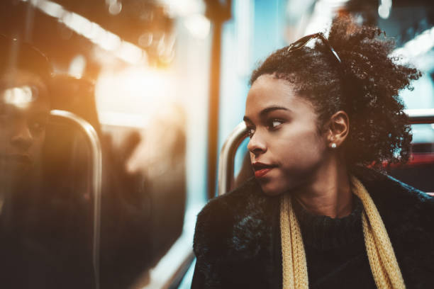 Biracial girl in a subway train The portrait of a young charming African-American female pensively looking outside the carriage window while sitting indoors of a metro train; Brazilian girl in a subway train, shallow depth of field introspection stock pictures, royalty-free photos & images