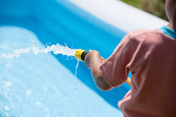 Biracial Little Boy Filling Up A Paddling Pool – Foto
