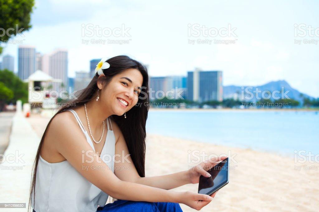 Biracial teen girl on beach using tablet computer, Waikiki, Honolulu royalty-free stock photo