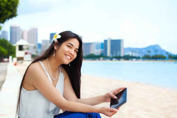 Biracial teen girl on beach using tablet computer, Waikiki, Honolulu stock photo