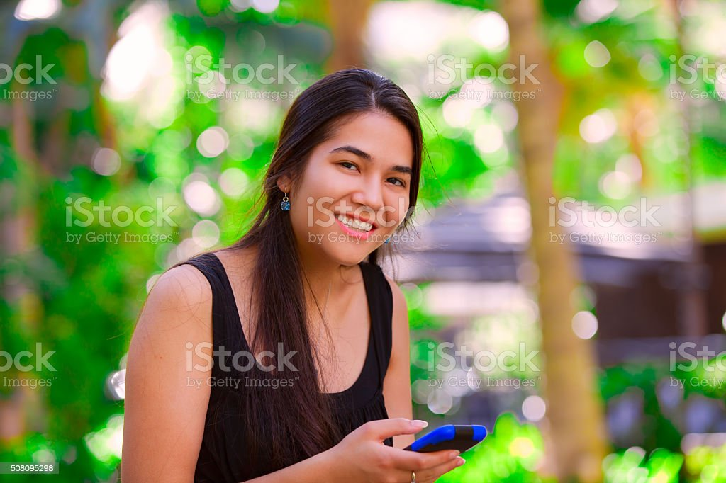 Biracial teen girl using  cellphone in tropical setting stock photo