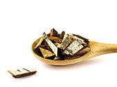 Birch bark in wooden spoon on white background.