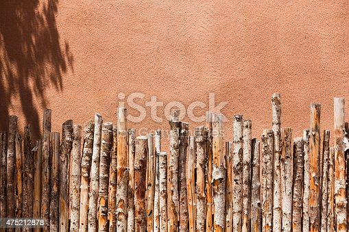 The southwest American native American style raw birch wood fence against a Adobe Wall texture background. Fence composed of straight birch wood branches, bundle in perfect rows, a popular style of outdoor fence in southwest America. Photographed on location in Santa Fe, New Mexico, USA, in horizontal format.