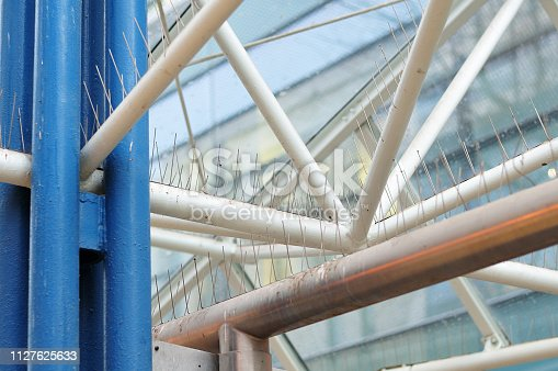 linkage of a modern pavilion in pedestrian zone of a city with bird control spikes
